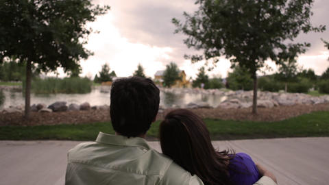A shot of a young, happy couple on a bench on a cloudy day Footage