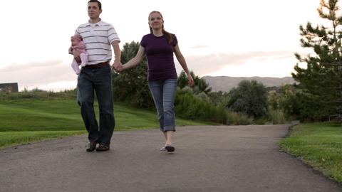 A shot of a couple slowly walking down a paved path through a beautiful park whi Footage
