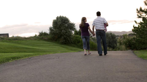 A tracking shot of the back of a couple walking through a park while the father  Footage