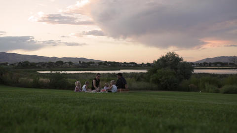 A tracking shot of a young family having a picnic by a lake on a cloudy day Footage
