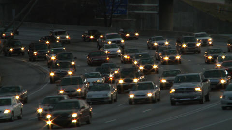 Static shot of traffic on the freeway while the sun barely lights the scene in A Footage