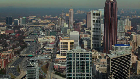A high angle, tilt shot of the Atlanta Skyline with cars flowing on the freeway  Footage