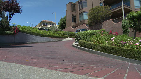 View of a couple cars driving the sharp turns on Lombard Street in San Francisco Footage