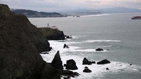 Zoomed view of jagged rocks and lighthouse with the waves crashing Footage
