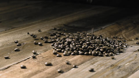 Coffee beans falling down on wooden table Footage
