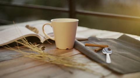 Cup of coffee with book and sunshine on background Live Action