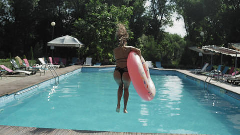 Young woman with inflatable rubber ring on summer vacation jumping into clear Footage