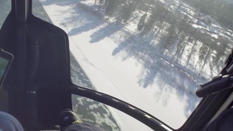 Point of view from pilot of a helicopter landing in ski touring lodge Live Action