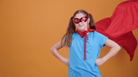 Cute young girl play superhero on a orange background background Footage