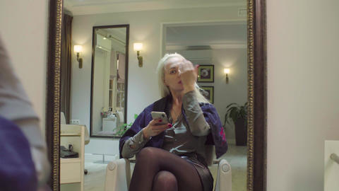 Attractive woman in salon looking in the mirror Live Action