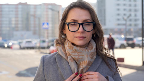 Portrait of a woman in glasses with a hairstyle and neutral makeup on a city Footage