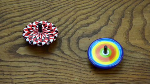 Two metal whirligigs toys on old oak wood table background Footage