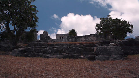 Static, wide shot of an ancient building in the shade surrounded by trees Footage