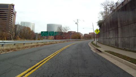 Driving down a road in Washington DC. Trees and buildings line each side of the  Footage