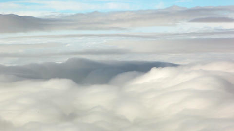 A panning shot of the top of a beautiful blanket of clouds against a grey and bl Footage