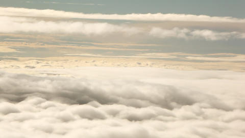 A panning shot of the top of a beautiful blanket of clouds against a grey sky Footage