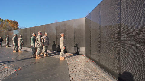A static shot of a soldier looking up at a wall of names of deceased soldiers in Footage