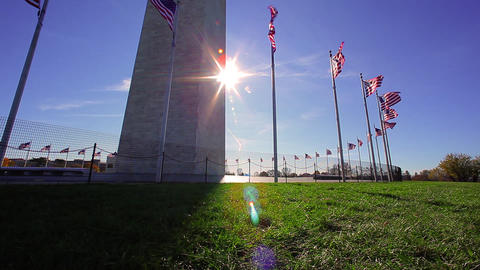 A tracking shot with a lens flare of american flags in front of the Washington M Footage