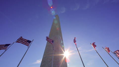 A static shot w/ lens flare of seven flags waving in the wind in front of the Wa Footage