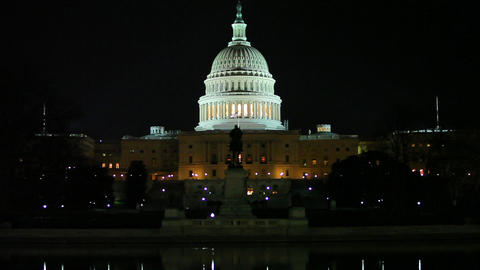 A static shot of the US Capitol with a historic statue in front of it at night Footage