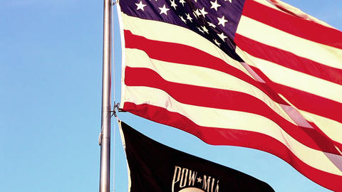 Close-up tilt shot of American and POW/MIA flags flying over Korean War Veterans Footage