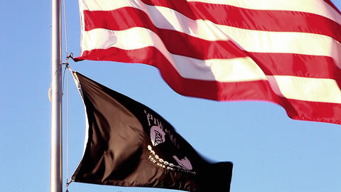 Tilting close-up shot of American and POW/MIA flags flying over Korean War Veter Footage