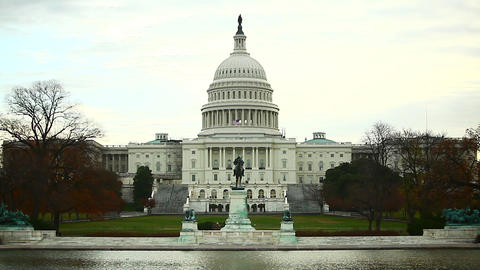 A full, static shot of the United States Capitol Dome Building against a blue, c Footage