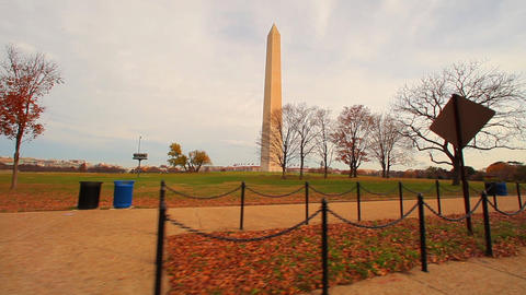 Tracking shot of the side of the Washington Monument with trees in foreground Footage