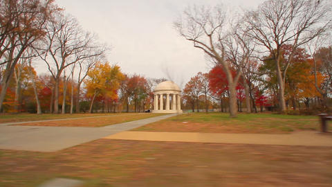 A panning shot of a memorial in a park during the fall in Washington DC Footage
