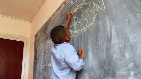Static shot of young boy drawing on chalkboard Live Action