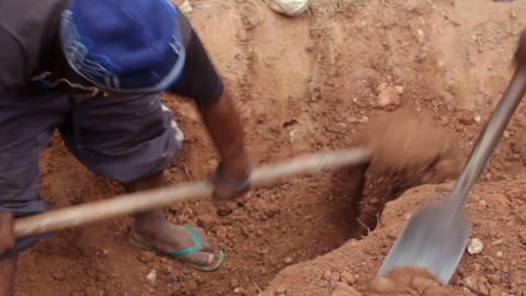 Man working hard shoveling dirt as he digs a hole Footage