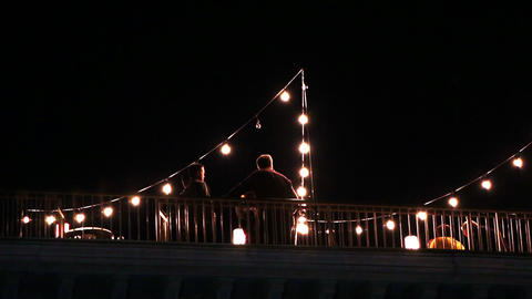 View of people on a deck outside at night with lights strung up around Footage