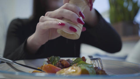 Young pretty girl with red manicure salt her delicious appetite dish sitting in Live Action