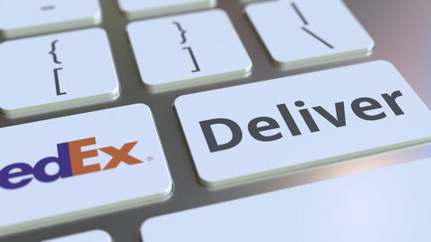FEDEX company logo and Deliver text on the keys of the computer keyboard Live Action