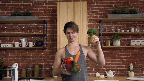 Young athletic vegan man holding broccoli and bowl with vegetable on the kitchen Footage