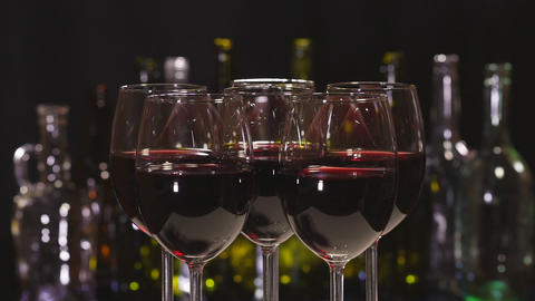 Red wine. Elegant wine glasses with red wine on the background of a row of alcohol bottles Footage