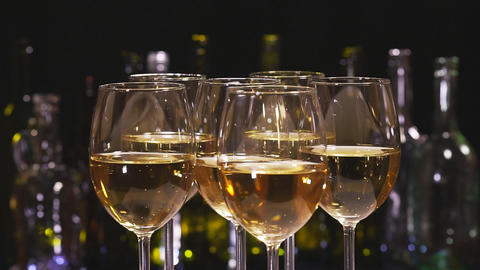 White wine. Elegant wine glasses with white wine on the background of a row of alcohol bottles Footage