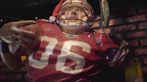 Manikin of the american football player in helmet and red uniform with ball Footage