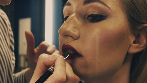 Professional makeup artist putting cosmetics on blonde model face Footage