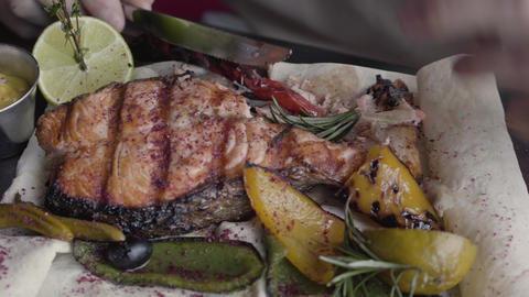 Close up big delicious dish of salmon fish grilled with vegetables, peper, lemon Live Action