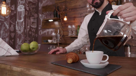 Cinemagraph gently filling a cup of fresh brewed coffee on a tray with a fresh Footage