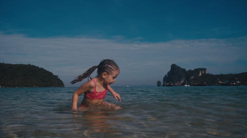 Little beautiful girl in swimsuit plays in warm summer sea. Water splashes Footage