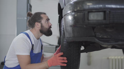 Handsome bearded mechanic inspecting suspension or brakes in car wheel of lifted Live Action