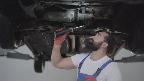 Successful bearded mechanic inspecting suspension or brakes in car with Live Action