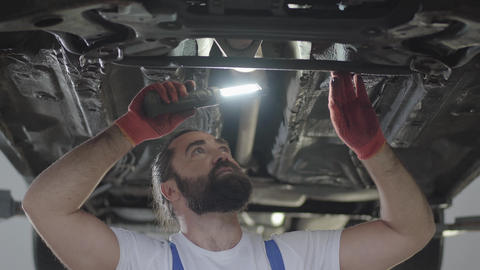 Bearded professional mechanic inspecting with lamp at repair service station Live Action