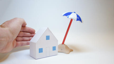 paper house that symbolizes vacation home and family, protected from the hands Live Action