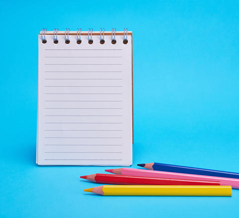 open blank notepad in line and multicolored wooden pencils Fotografía