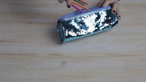 Women's hands quickly put pencils into the pencil case Footage