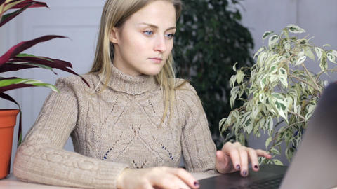 Girl is typing at his laptop around a lot of indoor plants Footage
