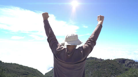 Man Reaching The Top. Jumping happy at the top of mountain. Achievement concept Live Action